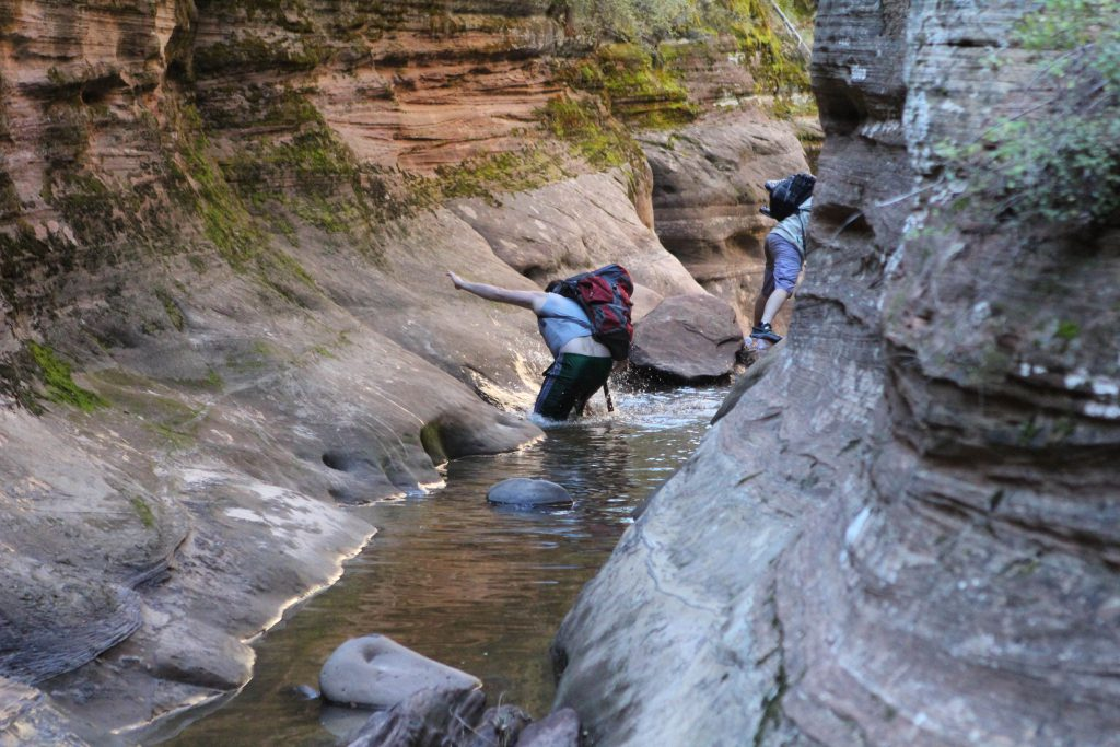 Nick Barkley Sliding into the Stream in Zion National Park photo by Brandy Little