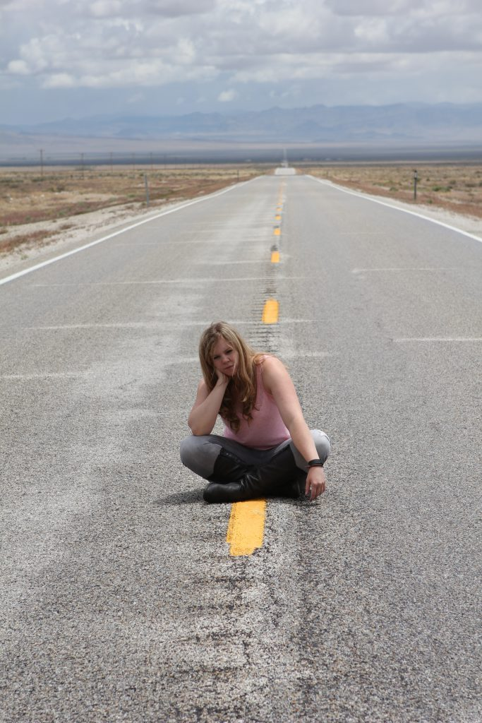 Brandy Little sitting on US Route 50, The Loneliest Road in America